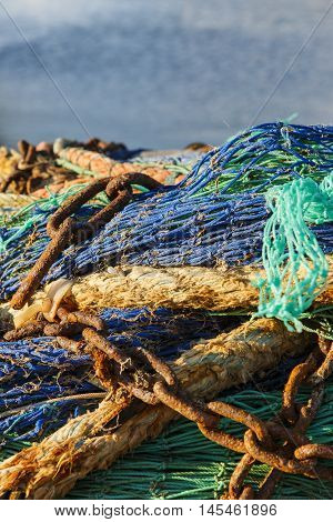 Fishing net with rusty chains with blue sea Close-up of green and blue fishing net with rusty chains and old ropes with blue sea on background