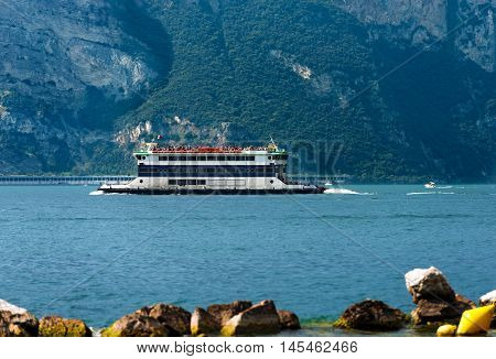 Ferry boat with tourists during navigation on Lake Garda near Malcesine Veneto Italy. In the background the coast of Lombardy
