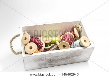 A wooden box with some spools with ribbon