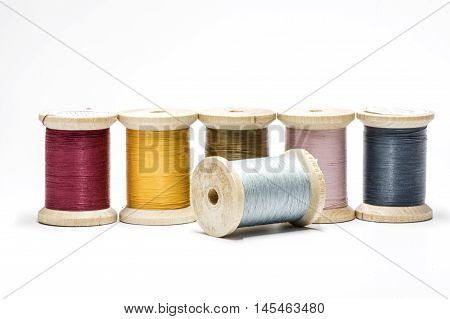 A row of spools with sewing threads