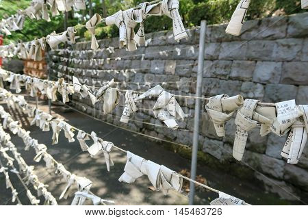 Kawagoe, Japan - August 15, 2015. Omikuji, random fortunes written on strips of paper at Shinto shrines and Buddhist temples in Japan, are tied to ropes in Kita-in temple in Kawagoe prefecture, Japan.