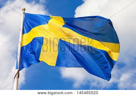 Swedish flag blue with yellow cross waving in the wind against a blue sky background with cloud
