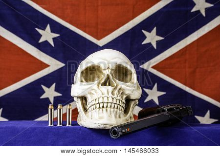 human skull with 357 magnum revolver and three bullets on blue with confederate flag background