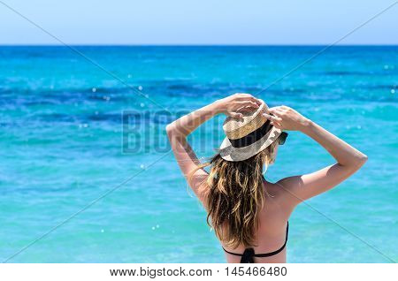 Portrait of young adorable caucasian woman in sunglasses and summer straw hat staying and reaching hands in sky over background of turquoise sea at tropical exotic sandy beach in Sardegna Italy