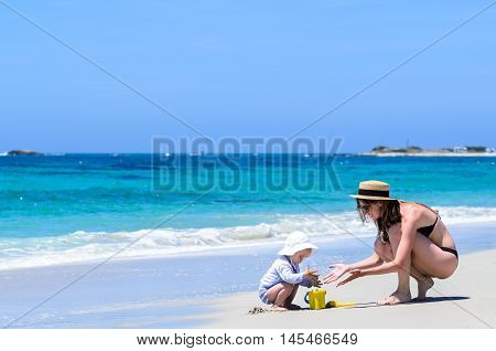 Young cute mother in sunglasses straw hat and swimwear and her adorable little daughter in swimsuit building sandcastles at tropical white sandy beach during vacation over background of turquoise sea