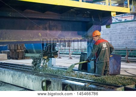 Tyumen, Russia - August 13, 2013: Block making department at construction material factory ZHBI-5. Workers operates machine on making of concrete plates