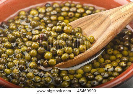 Bowl of green pepper grains close up