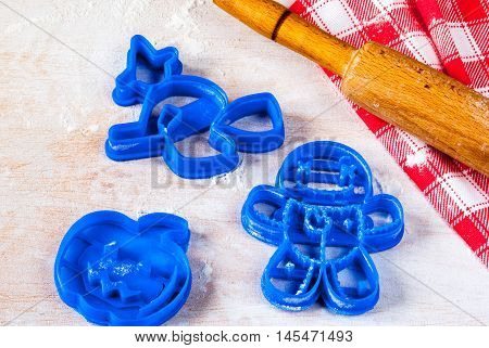 Making cookies for Halloween and Thanksgiving. Fun food for kids, a snack for a party. On a white wooden table cookie cutters, rolling pin, flour, towel