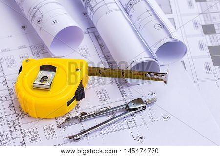 Tape measure and pencil compasses over a construction plan drawing for the project engineer jobs