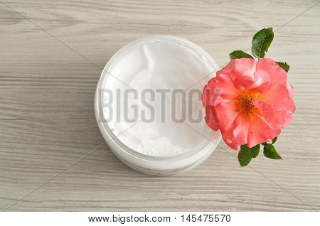 Body lotion in a plastic container with a pink rose top view