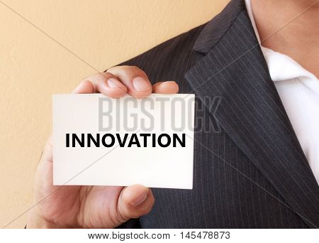 INNOVATION word on the white card presenting by a businessman