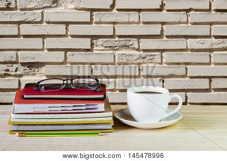 Coffee cup glasses and stack of book on wooden table with blur wall background. Business concept