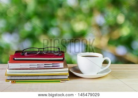 Coffee cup glasses and stack of book on wooden table with blur background. Business concept