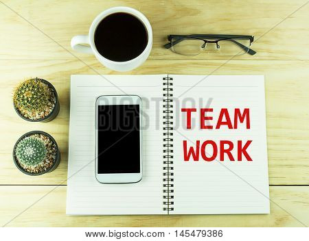 Smart phone coffeeglasses and book blank with cactus on wood table background. Text for TEAM WORK on a book.top view