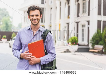 I prefer studying. Happy young man is holding textbook and laughing. He is standing near university