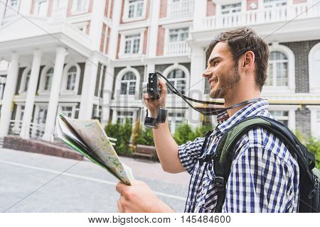 Happy young man is traveling around town. He is standing and photographing architecture with interest. Guy is holding map and smiling