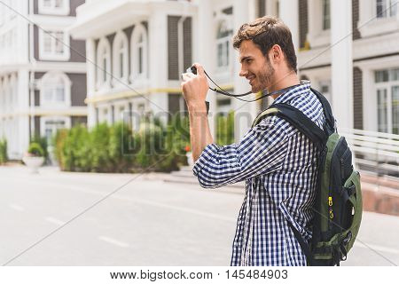 Carefree male tourist is photographing sightseeing in city with interest. He is standing and carrying rucksack. Man is laughing