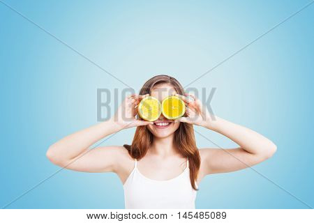Portrait of girl in white tank top holding sliced orange and standing against blue background. Concept of vitamins. Mock up
