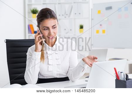 Business lady talking to her colleague on cell phone and explaining him their plan of actions for new week. Concept of business planning and development.
