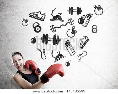 Portrait of woman boxer standing near concrete wall with sport icons on it. Concept of active sports and fitness