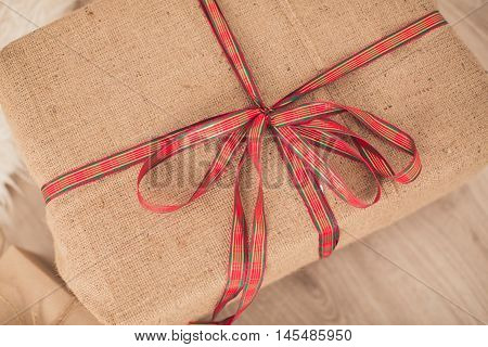 Gift box is packed into a sacking and tied up by a ribbon with a bow