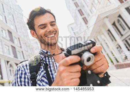 Happy young man is watching done shots with touristic places. He is holding camera and laughing. Traveler in standing on street in city