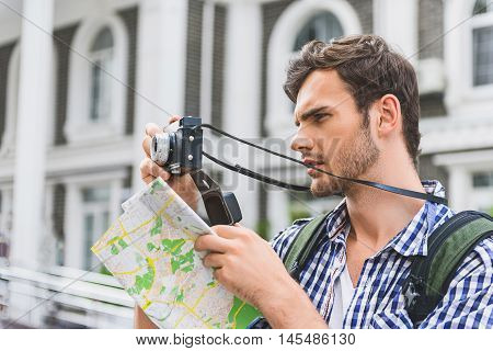 Pensive young man is photographing urban architecture with interest. He is standing and holding map