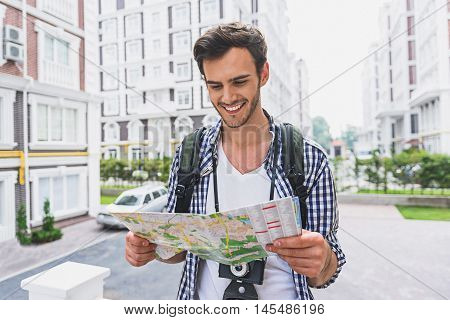 Inspired young man is ready to travel. He is looking at map with aspiration and smiling. Traveler is standing on street