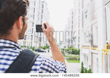 Carefree young man is taking photos of beautiful urban view. He is standing and looking forward with aspiration