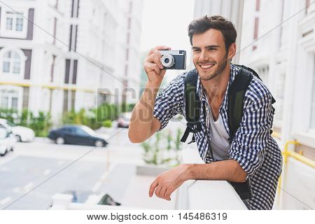 Young man is taking photos of city with inspiration. He is standing on balcony and holding camera. Traveler is smiling with happiness