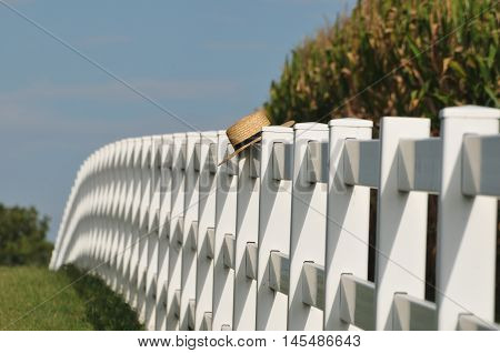 Amish straw hat laying over white picket fence near corn crops in Lancaster Pennsylvania