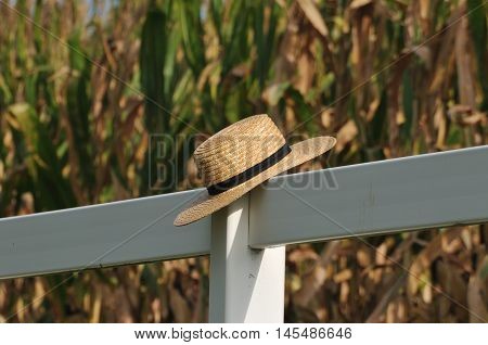 Closeup of Pennsylvania dutch Amish hat laying over white fence post with corn field behind