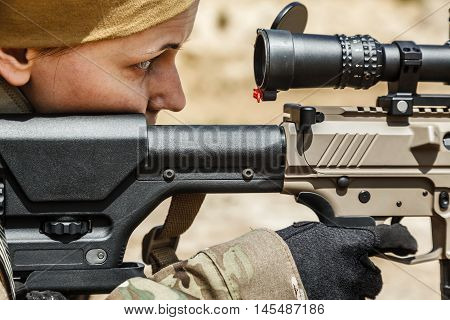 Young female sniper in camouflage with gun in the desert