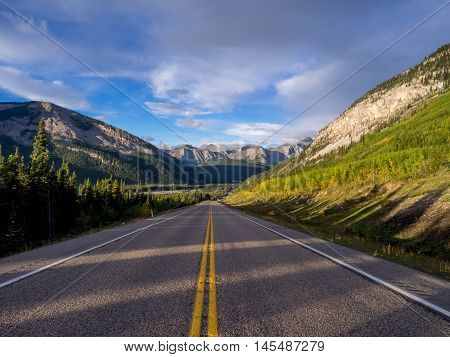 Beautiful landscape of a road through Rocky Mountains during the early hours of the morning.