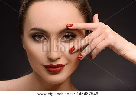 Flirty girl is touching her face with passion. She is standing and looking at camera confidently. Isolated