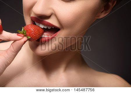 Flirty girl is biting strawberry with desire. Isolated