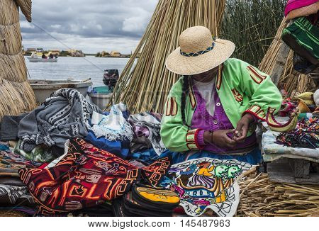 Uros Floating Islands Titicaca Peru - December 14 2014: Unrecognizable woman in national costume Indian Uros knits a sheaf