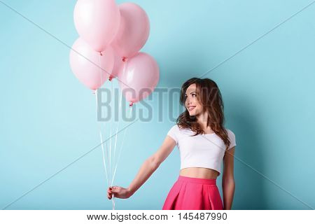 Joyful woman is holding balloons and smiling. She is standing and looking at present with excitement. Isolated