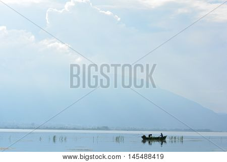 Fishing Boat In Lake With Cloudy Sky Reflection