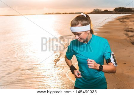 Young Sporty Girl Running On Beach At Sunrise In Morning