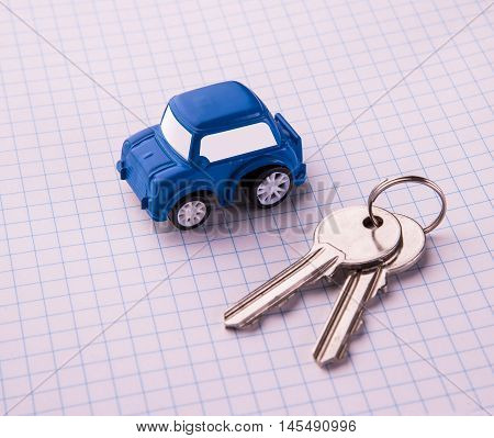 Blue Toy car and keys over white checkerd paper. Rent or buy car concept