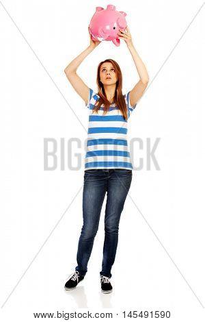 Sad teenage woman shaking piggybank for coins