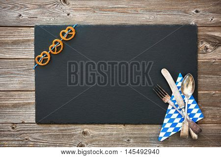 Bavarian silverware and pretzels on wooden board. Background for Oktoberfest