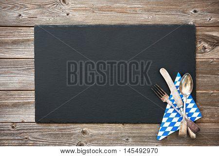 Bavarian silverware on wooden board. Background for Oktoberfest