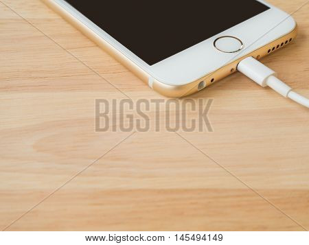 CHIANGRAI THAILAND -JULY 28 2016: Closeup image of the Apple iPhone 6 charging with Lightning USB Cable on the wooden table on July 28 2016 in Chiangrai Thailand.