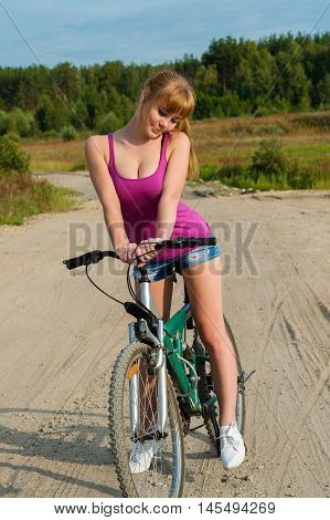 slender woman on bicycle outdoors on nature
