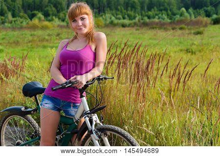 beautiful girl resting on bike on nature