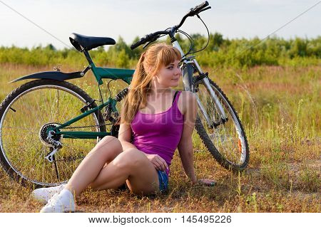 beautiful woman resting sitting on the grass with bicycle