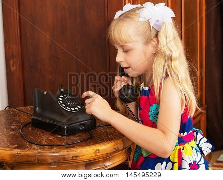 Adorable little blonde girl put your ear to the handset of the old phone. retro style