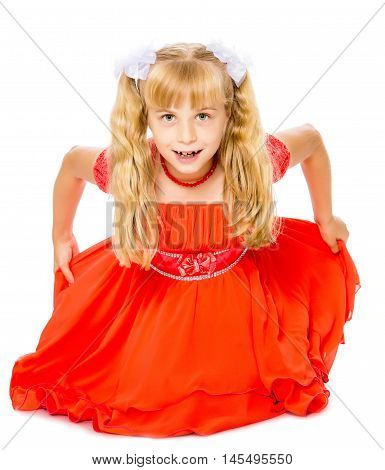 A beautiful little Caucasian girl with long, blonde ponytails on her head in a bright orange dress . Sat down on the floor-Isolated on white background